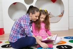 Mother reading book with her daughter at home Royalty Free Stock Image