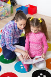 Mother reading book with her daughter at home Stock Photos
