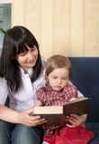Mother reading a book with her little daughter Stock Photography