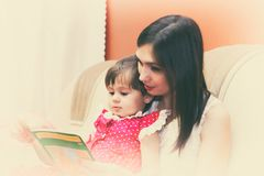 Mother reading a book with her little daughter. Toned photo stock image