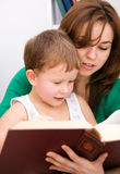 Mother is reading book with her son Stock Photography