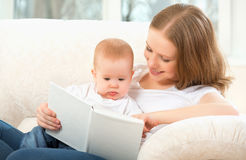 Mother reading a book a little baby on the sofa Stock Photography