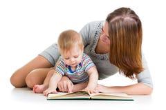 Mother reading a book to baby boy Stock Photos