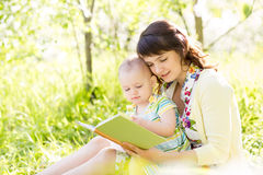 Mother reading a book to baby Stock Image