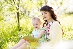 Mother reading book to baby outdoors Stock Image