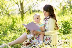 Mother reading a book to baby outdoors Stock Photography