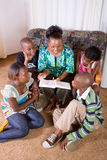 Mother reading book to children stock photo