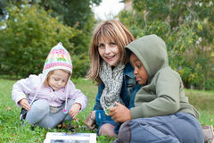 Mother reading a book to children Stock Photography