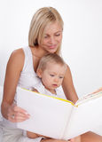 Mother reading book to a daughter Stock Images