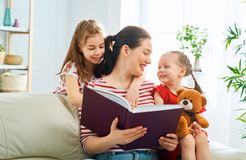Mother reading a book to daughters. Happy loving family. pretty young mother reading a book to her daughters stock image
