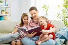 Mother reading a book to daughters. Happy loving family. pretty young mother reading a book to her daughters royalty free stock image