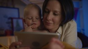 Mother reading book to her cute baby lieing on bed with differend pictures and give him treats flow camera stock footage