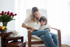 Mother,reading a book to her child, sitting in rocking chair royalty free stock photography