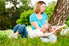 Mother reading book to her daughter Stock Image