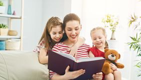 Mother reading a book to her daughters stock photography