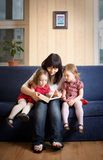 Mother reading a book to her little daughters Royalty Free Stock Images