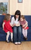 Mother reading a book to her little daughters Royalty Free Stock Photo