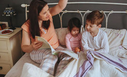 Mother reading book to her sons in the bed Royalty Free Stock Image