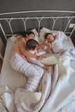 Mother reading book to her sons in the bed Stock Photo