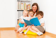 Mother reading book to her three age-diverse kids Stock Photos
