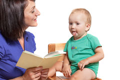 Mother reading a book to his mischievous kid. Isolated on white Royalty Free Stock Photos
