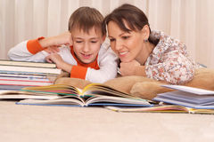 Mother reading a book to kid boy. At home Stock Photos