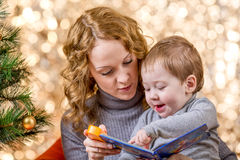 Mother reading book to kid at Christmas tree Stock Photo