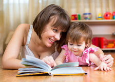 Mother reading a book to kid at home Royalty Free Stock Images