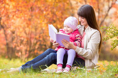 Mother reading  book to kid outdoor at autumn Royalty Free Stock Images