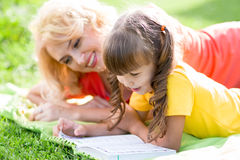 Mother reading a book to kid outdoors in summer Royalty Free Stock Photography