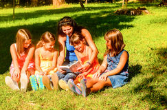 Mother reading a book to the kids. Mother is reading a book to her kids in the Park Stock Photo