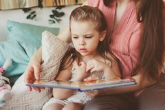 Mother reading book to toddler daughter in bedroom for good night. Casual lifestyle capture of happy family Royalty Free Stock Photography