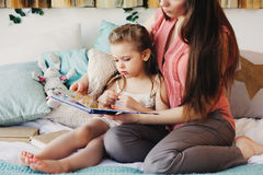 Mother reading book to toddler daughter in bedroom for good night. Casual lifestyle capture of happy family at home Stock Image