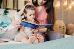 Mother reading book to toddler daughter in bedroom for good night. Casual lifestyle capture of happy family at home Royalty Free Stock Photos