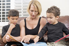 Mother reading book with two children Stock Photo