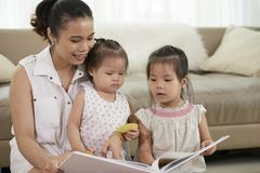 Mother reading for children stock images