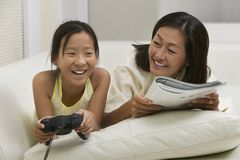 Mother reading on couch with Daughter Playing Video Game front view Stock Photography