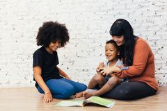 Mother reading a fairy tale fable story for kids at home. African American happy family concept. Mother reading a fairy tale fable story for kids at home stock image