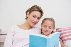 Mother reading her daughter bedtime story. At home in the bedroom Royalty Free Stock Photo