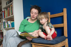 Mother reading with her son at home, casual, Stock Photo