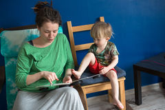 Mother reading with her son at home, casual, Royalty Free Stock Image