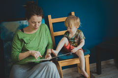 Mother reading with her son at home, casual, Royalty Free Stock Photos