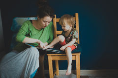 Mother reading with her son at home, casual, Royalty Free Stock Images