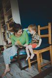 Mother reading with her son at home, casual, Stock Image