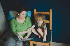 Mother reading with her son at home, casual, Royalty Free Stock Photo