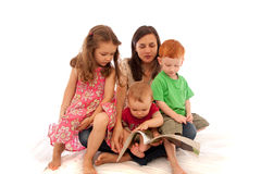 Mother reading kids book to children. Mum reading to three young kids on her lap Stock Photo