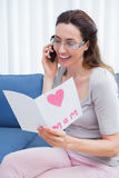 Mother reading a lovely card on phone call Stock Image