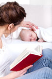 Mother reading beside sleeping baby Royalty Free Stock Photos