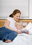 Mother reading son a bedtime story in bed. Devoted mother reading son a bedtime story in bed Stock Image