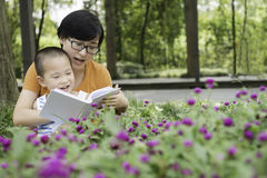 Mother reading for son. Chinese mother reading for son in garden Stock Photo